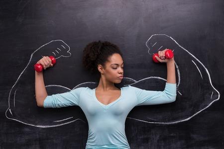 黒板背景にダンベルを持つ若いアフリカ系アメリカ人女性の面白い画像。黒板に描かれた 2 つの強力な筋肉の腕