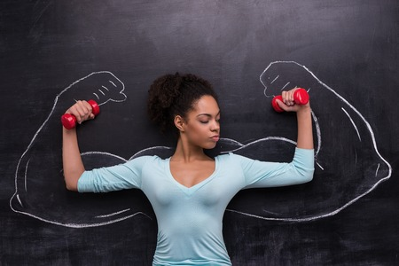 Funny picture of young afro-american woman with dumbbells on chalkboard background. Two strong muscular arms painted on chalkboard