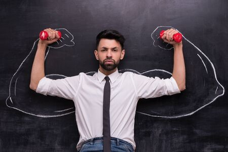 people development: Funny picture of serious businessman with dumbbells on chalkboard background. Two strong muscular arms painted on chalkboard Stock Photo