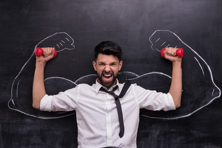 funny picture: Funny picture of young businessman with dumbbells on chalkboard background. Two strong muscular arms painted on chalkboard Stock Photo