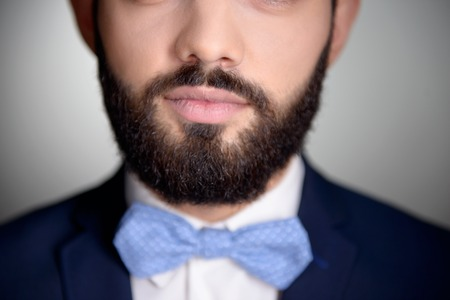 aucasian: Close up photo of handsome stylish man with beard. Man wearing classic dark blue suit and a blue bow tie