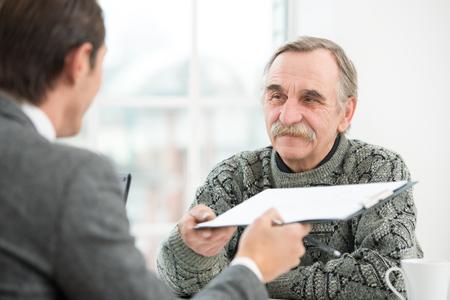 Giovane imprenditore con un colloquio o incontro di lavoro con il vecchio sorridente. Ufficio interno con grande finestra Archivio Fotografico - 37242043