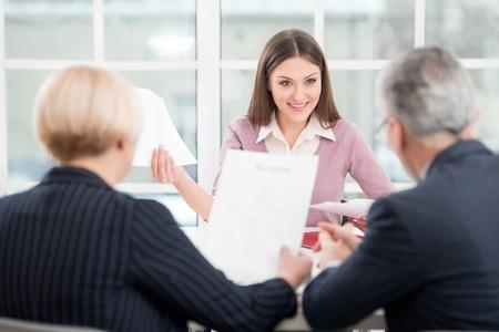 entrevista: Mujer joven que tiene una entrevista o reunión de negocios con los empresarios. Interior de la oficina con la ventana grande Foto de archivo