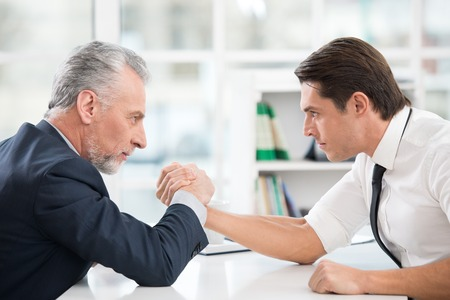 Two businessmen doing arm wrestling. Old one winning. Office interior with big window Stock Photo
