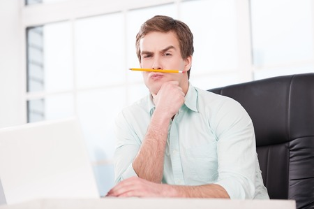 Funny picture of young businessman looking at camera and making moustache with pencil while sitting at his black leather office chair. Office interior with window Stock Photo