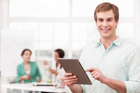 businessman working at his computer: Young smiling businessman looking at camera and using tablet computer. His creative team working on background. Office interior with window Stock Photo