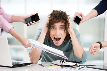 overworking: Shocked young businessman looking at camera. Hands with gadgets around him. Office interior with window. Concept for overworking