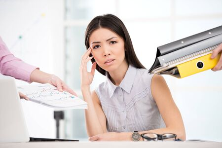 overworking: Tired young businesswoman looking at camera. Hands with folders around her. Office interior with window. Concept for overworking Stock Photo