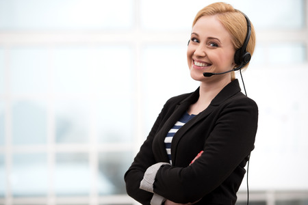 Young call center female operator looking at camera and smiling with headphones. Office interior with window