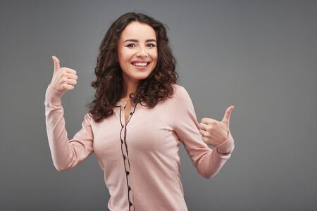 aucasian: Beautiful young woman smiling and showing thumbs up, standing on grey background Stock Photo