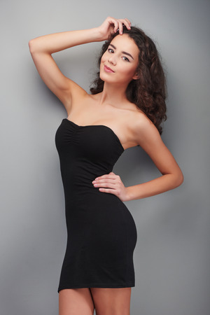 �aucasian: Beautiful young woman wearing black evening dress, standing on grey background
