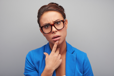 glance: Young mixed race woman with thoughtful glance wearing glasses, standing on grey background