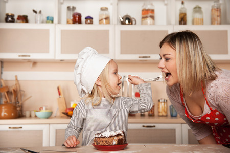 Little cute girl feeding her mother cake. Kitchen interior. Concept for young kitchen hands Stock Photo