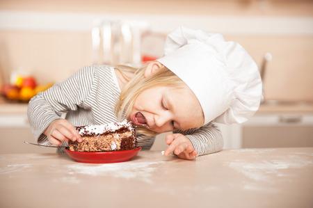 Menina bonito pequena que come o bolo com chap�u de chef. Interior da cozinha. Conceito para jovens m�os de cozinha
