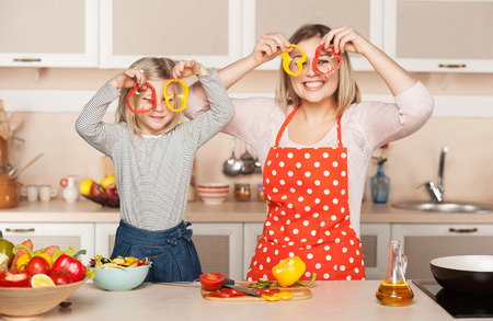 making fun: Beautiful smiling young mother and her little daughter having fun while cooking salad. Kitchen interior. Concept for young kitchen hands