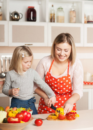 making fun: Beautiful smiling young mother helping her little daughter to chop paprika while cooking salad. Kitchen interior. Concept for young kitchen hands