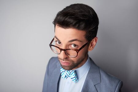 steadily: Portrait of elegant casual young man with glasses wearing jacket and bow tie. Man looking steadily and intently at camera