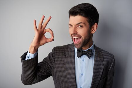 ok sign: Portrait of positive casual young man wearing jacket and bow tie. Man smiling, winking and showing ok sign Stock Photo