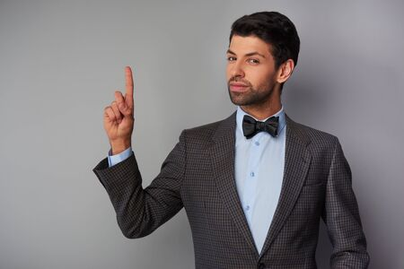 man pointing up: Portrait of elegant casual young man wearing tweed jacket and bow tie. Man pointing up and looking at camera
