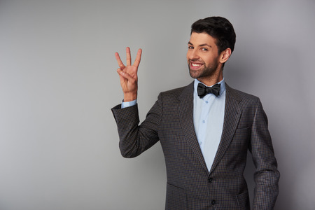 Portrait of positive casual young man wearing tweed jacket and bow tie. Man smiling, showing three fingers and looking at camera Stock Photo