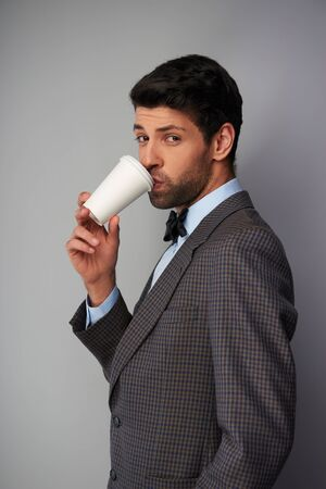 tweed: Portrait of elegant casual young man wearing tweed jacket and bow tie. Man drinking coffee in a white cup and looking at camera Stock Photo