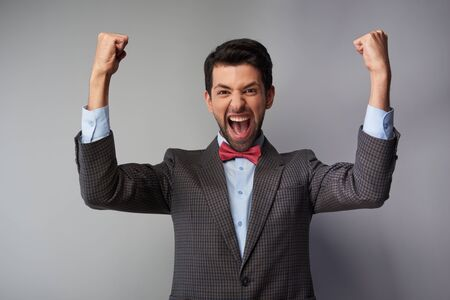 tweed: Portrait of very happy and positive casual young man wearing tweed jacket and red bow tie Stock Photo