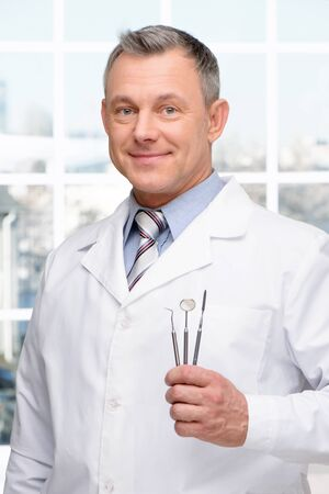 aucasian: Photo of dentist holding stomatologist tools and looking at camera. Concept for teeth hygiene