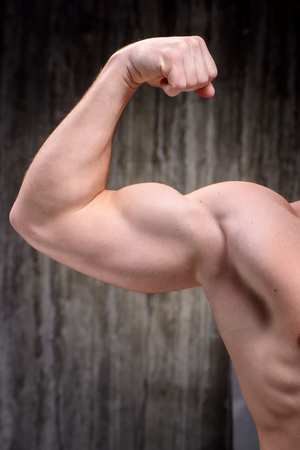 formed: Close up photo of young well formed sporty man demonstrating biceps. Stock Photo