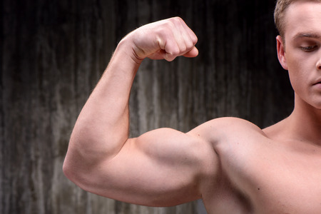 formed: Close up photo of young handsome well formed sporty man demonstrating biceps. Fitness concept