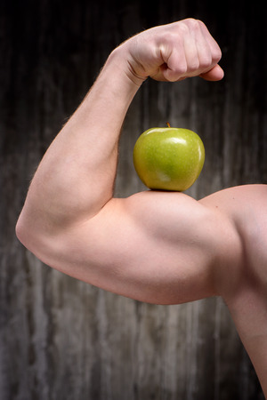 formed: Close up photo of young well formed sporty man demonstrating biceps with green apple on it. Fitness and healthcare concept