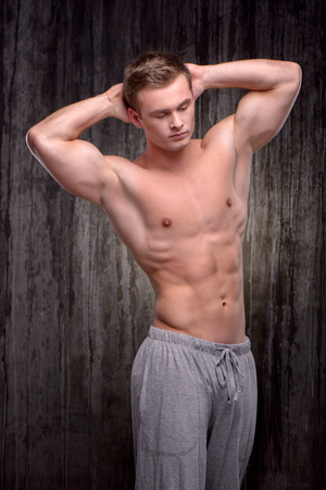 aucasian: Young handsome well formed sporty man demonstrating muscles with his arms raised up. Fitness concept