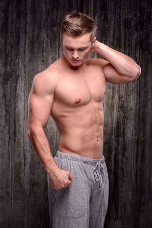 formed: Young handsome well formed sporty man demonstrating muscles with his arm raised up. Fitness concept