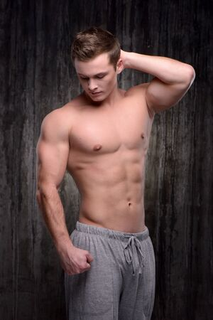 aucasian: Young handsome sporty man demonstrating muscles with his arm raised up. Fitness concept