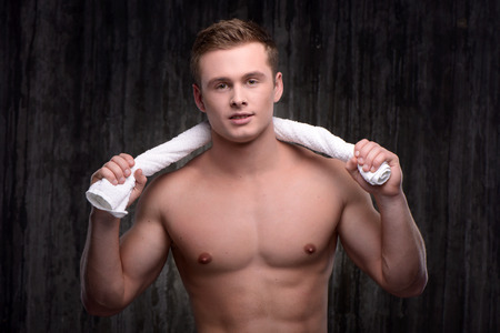 formed: Photo of young handsome sporty well formed man after workout. Man holding white towel and looking at camera Fitness concept Stock Photo