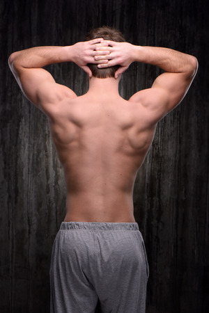 aucasian: Back view photo of young well formed sporty man demonstrating back muscles. Fitness concept