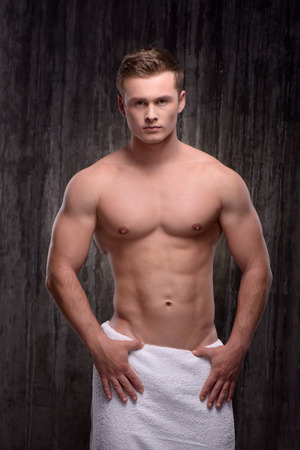 aucasian: Young handsome well formed sporty man with white towel on his hips looking at camera. Fitness concept