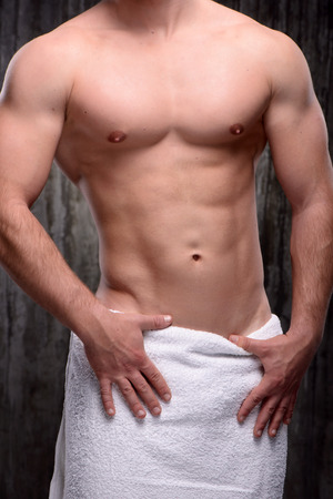 formed: Close up photo of young handsome well formed sporty man with white towel on his hips. Fitness concept Stock Photo