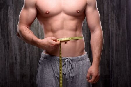 formed: Close up photo of young well formed sporty man measuring his waist with yellow tape. Fitness concept Stock Photo