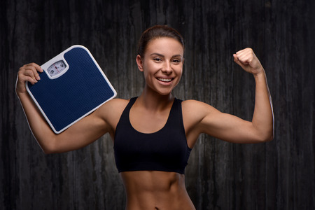 weighs: Young mixed race sporty woman wearing black tracksuit for training. She cheerfully smiling, demonstrating biceps and holding weighs. Fitness and healthcare concept Stock Photo