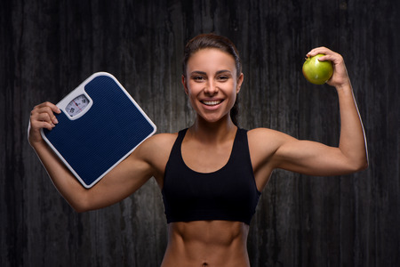 weighs: Young mixed race sporty woman wearing black tracksuit for training. She cheerfully smiling, holding weighs and apple. Fitness and healthcare concept