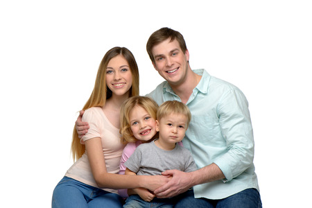 family portrait: Cheerful smiling young family of four enjoying time together and looking at camera.
