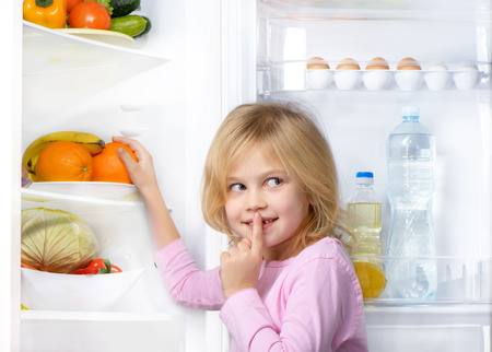 Little cute girl making silence sign and picking food from fridge. Vegetables and fruits in the refrigerator