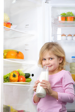 Little cute girl looking at camera and holding bottle of milk near open fridge. Vegetables and fruits in the refrigerator