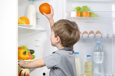 Little cute boy picking orange from fridge. Vegetables and fruits in the refrigerator