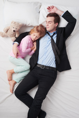 bed time: Top view photo of tired businessman wearing suit, and his little cute daughter. Stock Photo