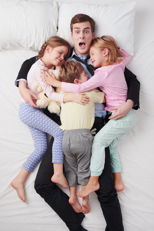 Top view photo of shocked businessman wearing suit, and his three children. Fathers arms are over daughters and son. Chidren sleeping on father and hugging each other