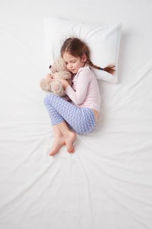 Draufsicht Foto des kleinen netten Mädchens auf weißem Bett schläft mit Teddybär. Ruhige Fötus darstellen. Konzept der schlafenden Posen