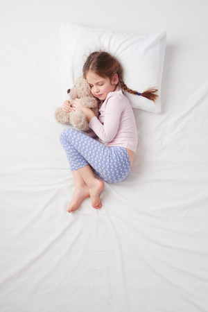 Top view photo of little cute girl sleeping on white bed with teddy bear. Quiet Foetus pose. Concept of sleeping poses