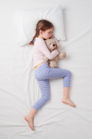 sleeping animals: Top view photo of little cute girl sleeping on white bed and hugging teddy bear. Stock Photo