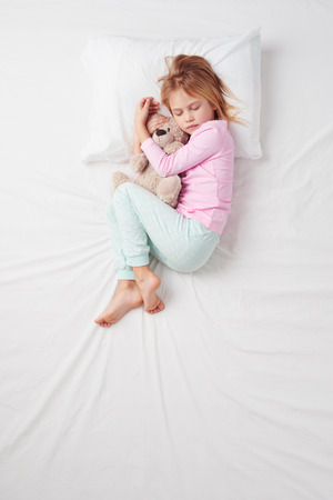 Top view photo of little girl sleeping on white bed with teddy bear.